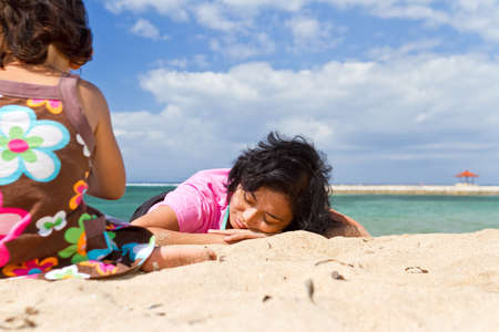 asian ethnic mother relaxing with child playing at the beach photo