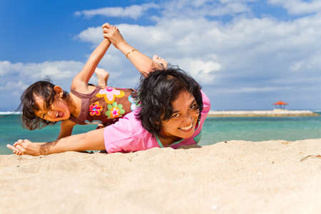 Asian ethnic mother and child happy palying together at the tropical beach photo