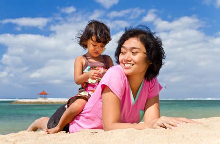 Asian ethnic mother and child happy playing together at tropical beach photo