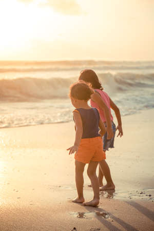 seashores: asian ethnic children exploring the seashore at sunset