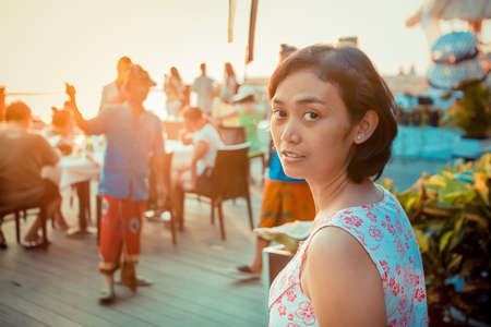 amongst: asian ethnic youg woman having leisure time amongst people on her vacation at bali tropical island Stock Photo
