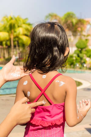 girl care: Mother Hand Putting Sunblock Lotion on Little Girl Back Skin Before Swimming