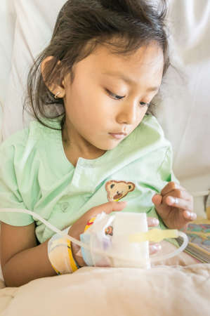 impatient: Asian Ethnic Little Girl Feeling Depressed Infusion Impatient in Hospital Stock Photo
