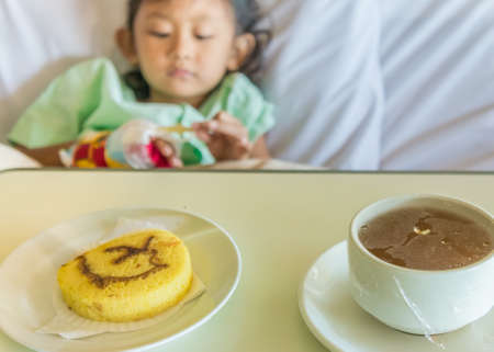 impatient: Sick Asian Ethnic Little Girl Hospital Impatient Resting on Bed Served with Lunch Meal Menu on the Table Stock Photo