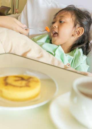 fond of children: Sick Asian Ethnic Little Girl Hospital Patient Having Breakfast on Bed