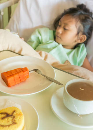impatient: Sick Asian Ethnic Little Girl Hospital Impatient Resting on Bed Served with Breakfast Meal Menu on the Table