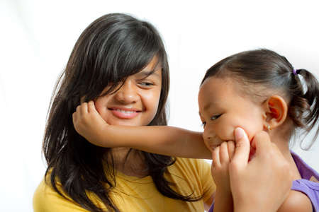 child smile: Two lovely Asian sisters playing together