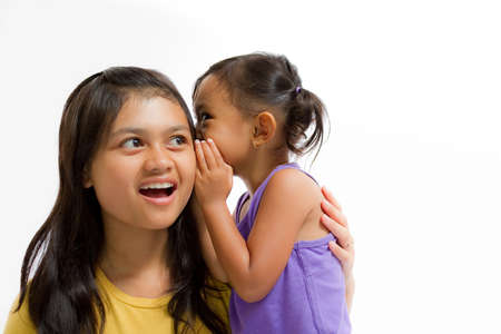 Asian Little Girl Whispering Something to Teen Sister Isolated on White photo