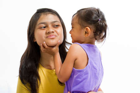 Asian Little Girl Playing Fun Games Together with Teen Nanny photo