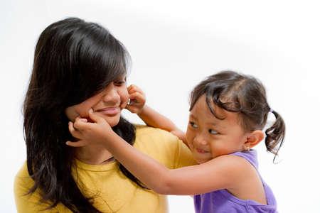 pinch: Asian Little Girl Pinch Teen Sister Cheek Stock Photo