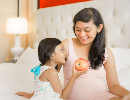 Happy Asian Pregnant Mother and Little Girl Offering Healthy Apple photo