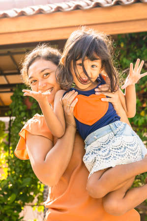 Portrait of Happy Asian Mother Fun Together with Her Little Girl photo