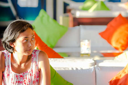 Portrait of Asian Young Woman Sitting and Waiting Alone in a Cafe photo