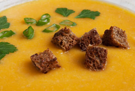 Pumpkin soup with crackers close up view