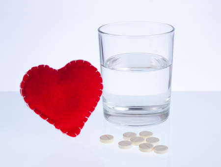 Red heart, glass of water and pills Stock Photo