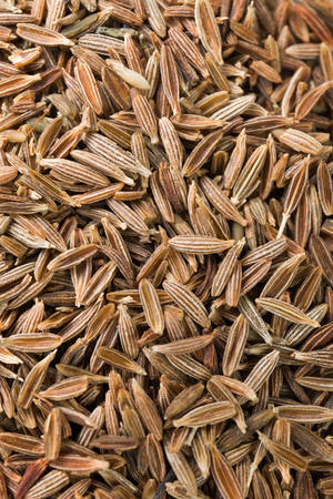 Cumin fragrant spice dry seeds. Textured food background. Top view