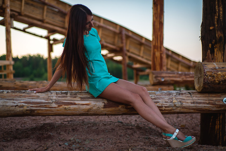 girl in turquoise short dress sitting on a tree log. Summer