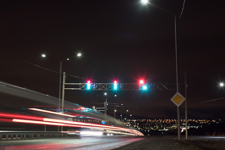 Time exposure photo with a street at night and automobile headlights and traffic light. Crossroads. Timber carrying vessel