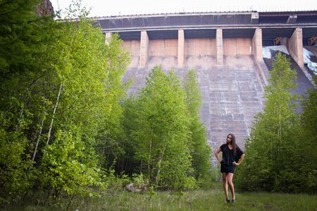 A dreamy young brunette girl stay near hydroelectric power station. Evening time. Side view.