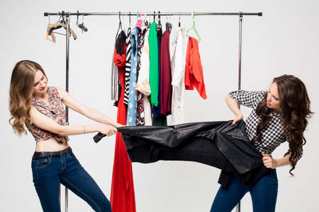 COSTUMERS: Two women fighting over shopping bag with furious expressions.