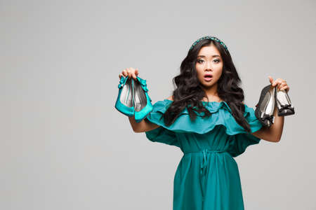 cant: Woman keeps two high heeled shoes and cant choose the one for her. Portrait of beautiful young woman with shoes.