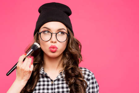 Young hipster girl having fun and going crazy, wearing glasses hat and bright make up. Pink urban background. The woman made his lips in a kiss ,make up, make up girl, puffed out his cheeks.