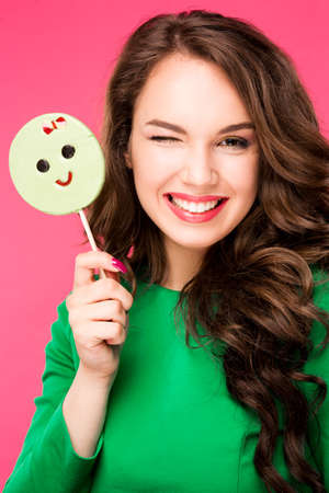 broadly: Beautiful young woman holds in hands candy smiling broadly. Stylish girl with bright makeup and candy in her hands, isolated on pink background.