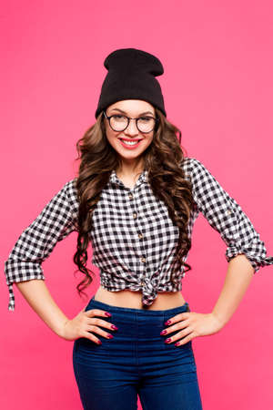 beleza: Beauty fashion sexy girl wearing glasses, pink background, hipster outfit, hat, plaid shirt, jeans, smiling white teeth.