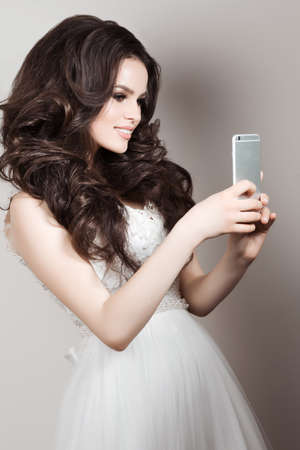 taking a wife: Pretty smiling bride in wedding dress posing when tacking photo herserself on smart phone. Brunette girl with long curly hair and perfect make up taking selfie on her call phone. White background.
