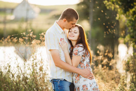 love park: Portrait of happy and young couple standing on pier of lake at sunset and embracing. Side view of handsome husband kissing his brunette wife. Romantic atmosphere outdoor in summertime.