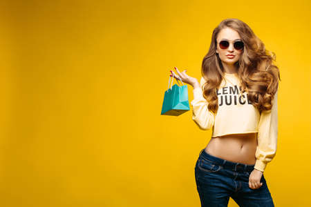 Fashionable sexy brunette woman with volumed wavy hair holding little blue paper bag with present, after shopping and posing at camera. Stylish woman in sunglasses and yellow crop sweatshirt. Stock Photo
