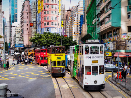 hk: A colorful street photo showing the double-decker trams on Hong Kong Island, locally known as Ding Dings. A busy urban scene. Editorial