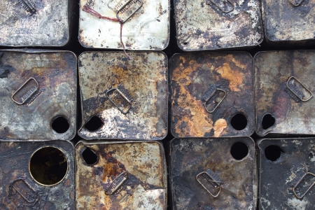 Many old gallons of oil is stacked outdoors  photo