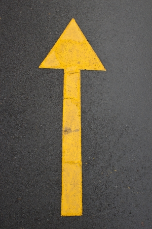 wet yellow arrow road or concept and slippery Imagens