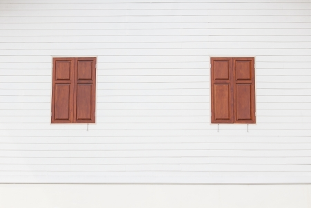 two brown wooden windows on white wooden house photo