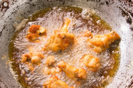 Frying chicken drumstick in boiling oil iron pan photo