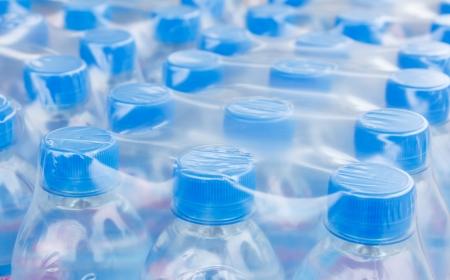 Rijen van flessen water in plastic folie Stockfoto