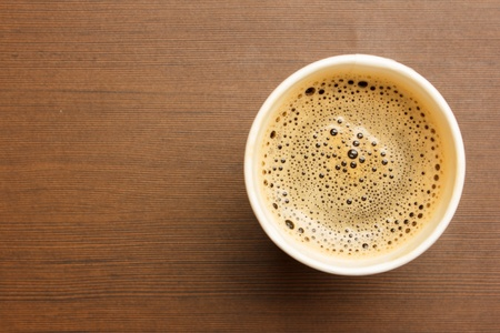 Top view of a paper cup of black coffee on wooden table