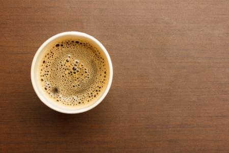 木製のテーブルの上のブラック コーヒー紙コップのトップ ビュー 写真素材