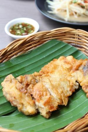 batter-fried chicken Breat on a banana leaf with sauce photo