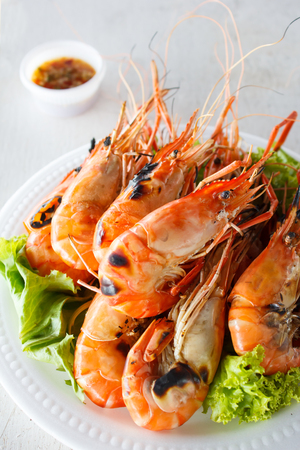 Grilled prawns with seafood sauce on white wood photo