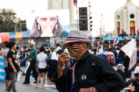 An unidentified old man blow a whistle in Anti-government protest at Democracy Monument on November 21, 2013 in Bangkok, Thailand. The protest Against The Amnesty bill in capital of Thailand