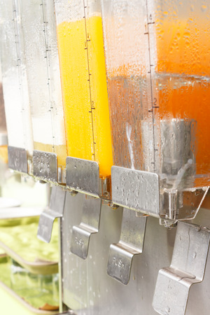 Orange juice and drinking water in dispenser photo