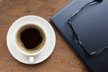 Top view of coffee cup , glasses and laptop on wooden table photo