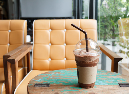Iced chocolate shake on wooden table at coffee shop photo