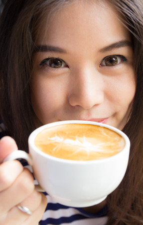 Close up of asian woman smiling and holding cup of  cappuccino coffee photo
