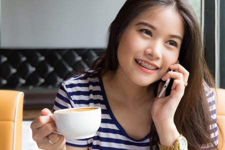 Beautiful woman talking on the phone and  holding cup of coffee at cafe Imagens
