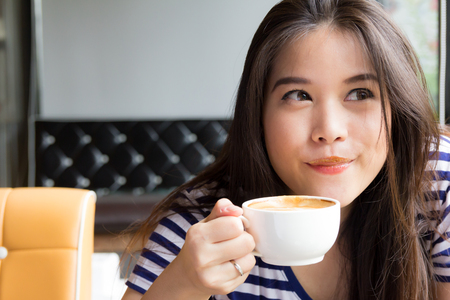 coffee stain: Asian woman smiling and drinking coffee at cafe
