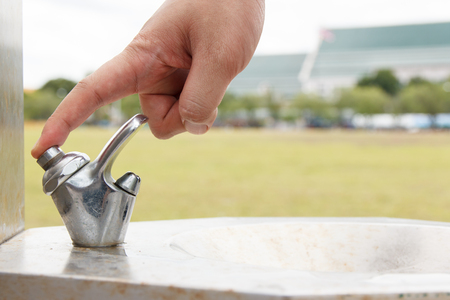 clean off: hand man push button of drinking water faucet  Stock Photo