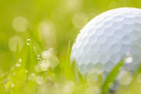 Close up Golf ball on grass with water drops and bokeh